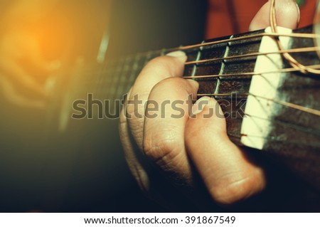 playing acoustic guitar close-up.old film processed for vintage photo style - stock photo