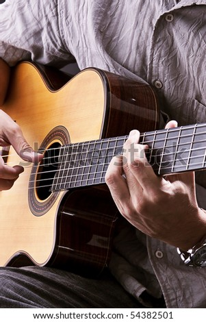 Playing acoustic guitar. Studio photography. - stock photo