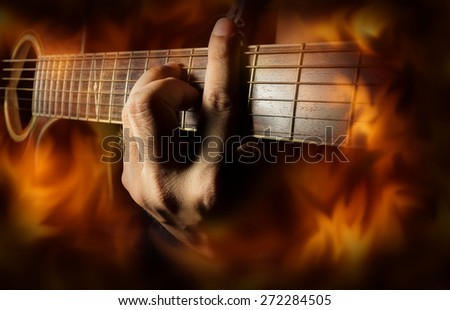 Playing acoustic guitar with fire flame screen. - stock photo