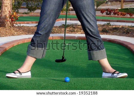 Playing Adventure Golf, downhill shot, ball, club and hole. - stock photo