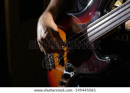Playing an bass guitar - stock photo