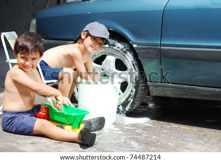 Playing around the car and cleaning, children in summertime - stock photo