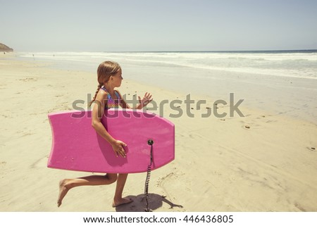 Playing at the beach on summer vacation running into the ocean with a boogie board - stock photo