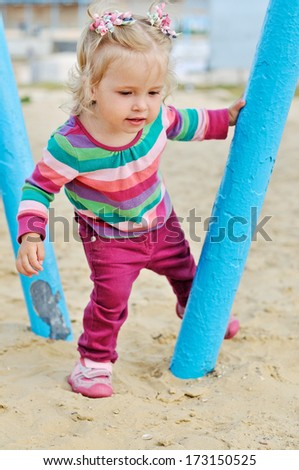 playing baby girl on the sand - stock photo