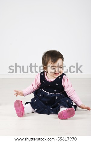 Playing baby girl sitting on floor looking down and laughing,copy space for text message - stock photo