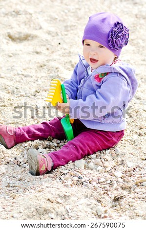 playing baby girl sitting with rake on the beach - stock photo