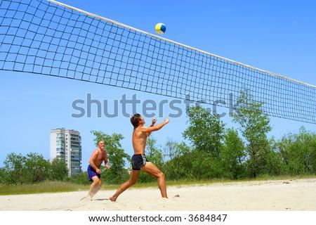 playing beach volleyball. Shot near Dnieper river, Ukraine. - stock photo