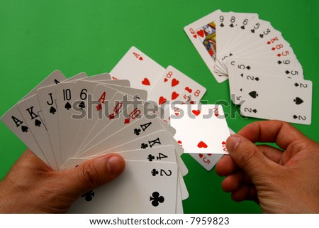 "playing bridge - one hand (A,K,J,10,6 spades, 2 heart, A,Q,10 diamonds, A,K,4,2 clubs),  on table other ""bridge hand"" - stock photo"