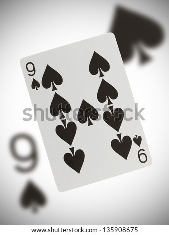 Playing card with a blurry background, nine of spades - stock photo
