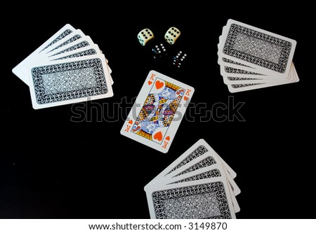 Playing cards and dices on black background - stock photo
