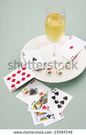 Playing cards and dices with glass of champagne - stock photo