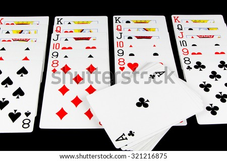 Playing cards being used for solitaire on black background