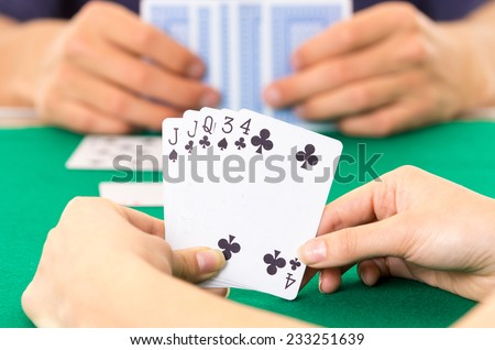 Playing cards closeup of hands holding deck cuarenta traditional Ecuadorian game selective focus - stock photo