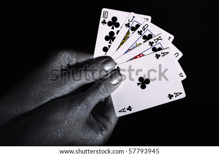 Playing cards in the silver male hands on black background close up