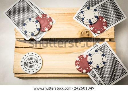 Playing cards lying on a wooden support together with dealer and blind buttons - stock photo
