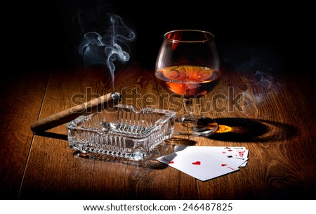 Playing cards near wineglass of whiskey and cigar - stock photo