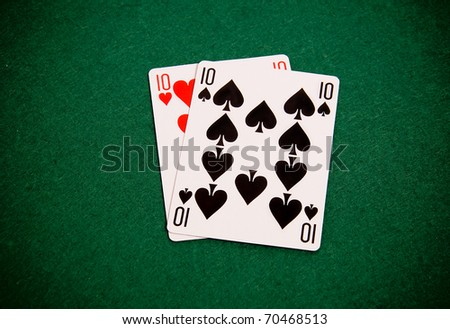 Playing cards on green background, pair of tens - stock photo