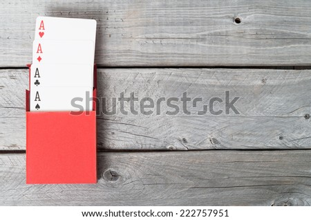Playing cards on wooden background, four aces - stock photo
