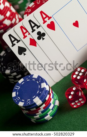 Playing cards, poker chips, and dices on green table