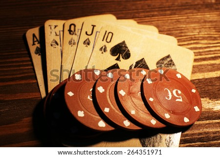 Playing cards with chips on wooden table, closeup - stock photo
