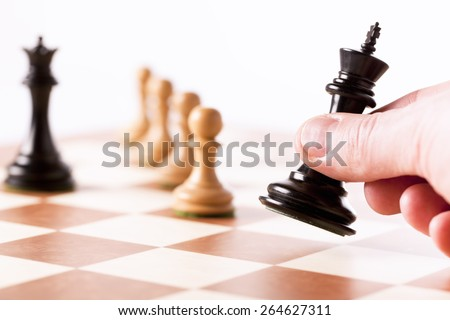 Playing chess game - a hand moving the black king with white pawns in perspective - stock photo