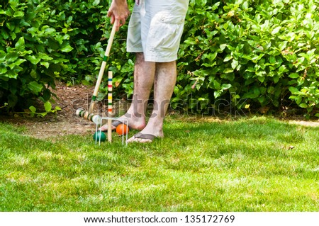 Playing Croquet : Man getting ready to hit ball with mallet - stock photo