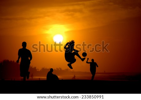 Playing football at the sunset on the beach - stock photo