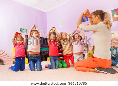 Playing game and group of kids show home with hand - stock photo