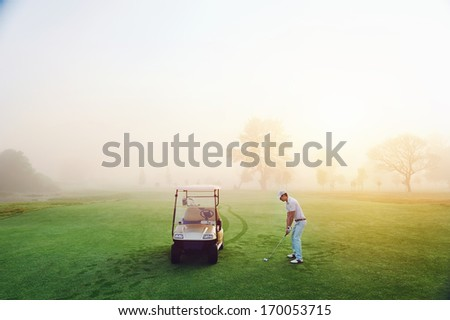 playing golf on the fairway with cart in the morning sunrise and misty dew grass - stock photo