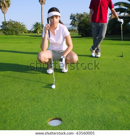 playing golf young woman looking and aiming for the hole - stock photo