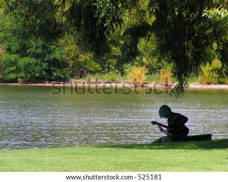 Playing guitar beside a lake - stock photo