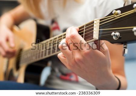 Playing guitar close up with selective focus  - stock photo