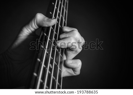 Playing guitar or bass with fingers on fretboard with dark background and copy space. - stock photo