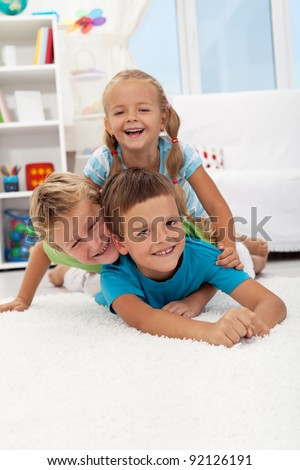 Playing happy children laying on the floor in a heap and laughing - stock photo