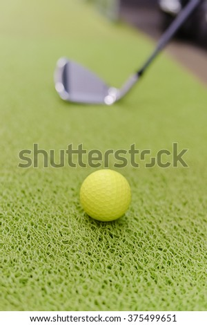 Playing indoors. Golf club and ball on green carpet grass background texture - stock photo
