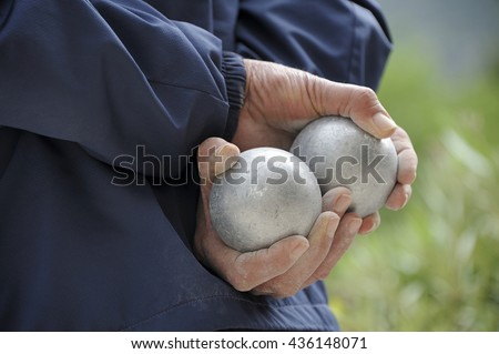 Playing jeu de boules or also called petanque in France. This play is played at street in every village of France.