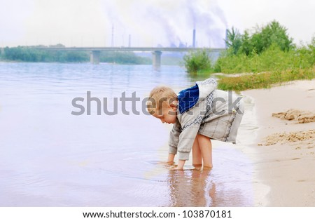 Playing little boy on the river coast near industrial plant - stock photo