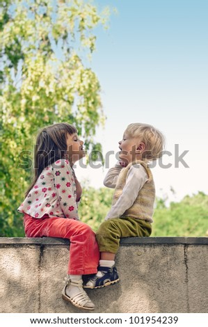 playing little girl and boy in the park - stock photo