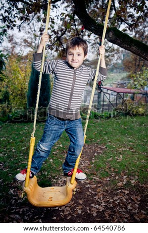 Playing on a swing in the backyard - stock photo