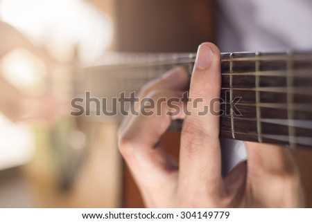 Playing on acoustic guitar. Close-up.