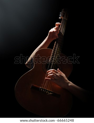 Playing on acoustic guitar on a black background - stock photo