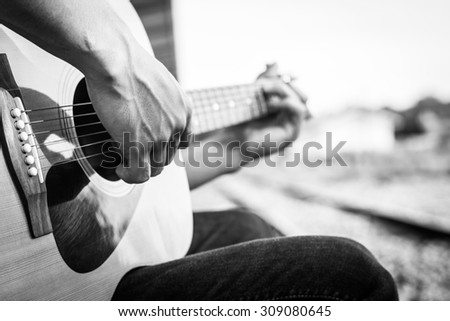 Playing on acoustic guitar outdoor. Black and white photo - stock photo