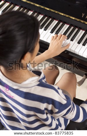 playing piano, asian teenage girl playing piano. - stock photo