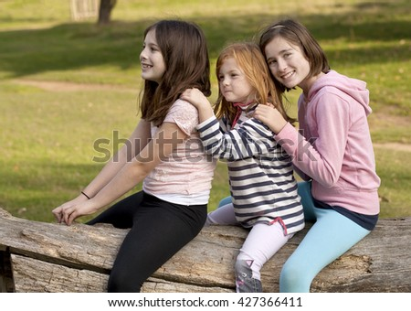 Playing Pretend. Three sisters are straddled over a fallen dead tree trunk, playing pretend that they are riding off on a horse. They are all amused by their game.  - stock photo