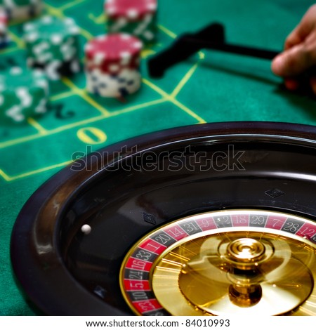 Playing roulette with a moving roulette with a green table with chips - stock photo