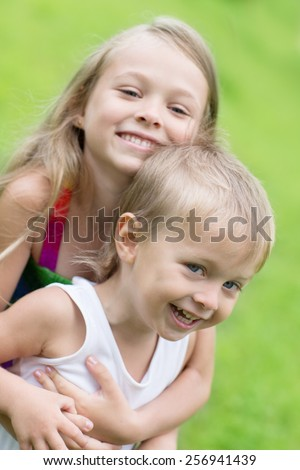 Playing sister and younger brother on the lawn. Children three and seven years. - stock photo
