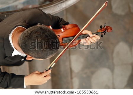 Playing the violin. Musical instrument with performer hands - stock photo