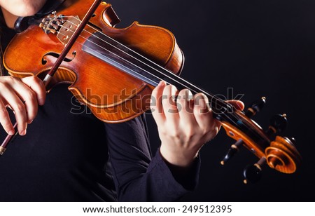 Playing the violin. Musical instrument with performer hands on dark background - stock photo