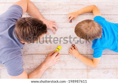 Playing together. Top view of father and son lying on the hardwood floor and playing with toy cars together  - stock photo