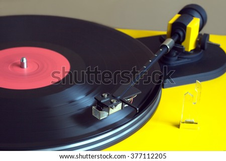 Playing vinyl LP record with red label on vintage turntable record player with yellow case. Horizontal photo closeup
